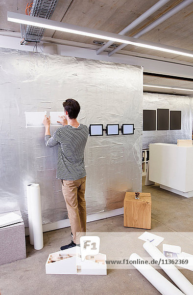 Architect in office looking at blueprint on wall