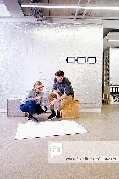 Architekten im Büro diskutieren über Entwürfe