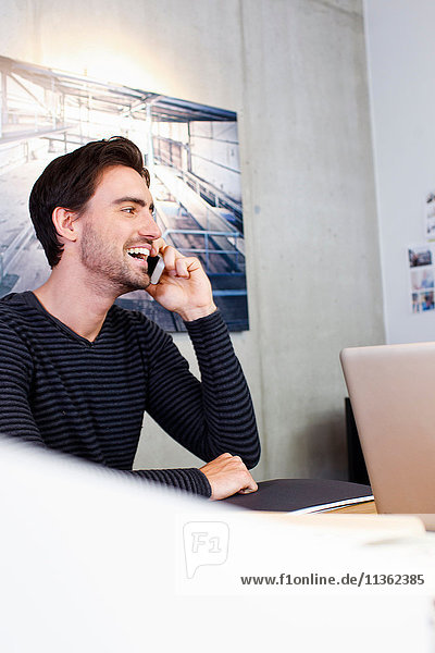 Man in office using mobile phone  looking away smiling