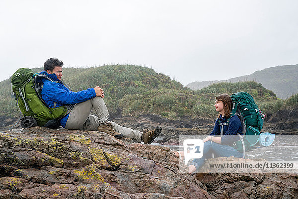 Junges Paar mit Rucksack  auf Felsen sitzend  Constant Bay  Charleston  Südinsel  Neuseeland