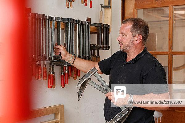 Mann wählt Handwerkzeug aus