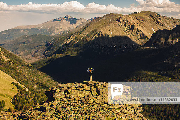 Rear view of woman on rocky outcrop looking away  Rocky Mountain National Park  Colorado  USA
