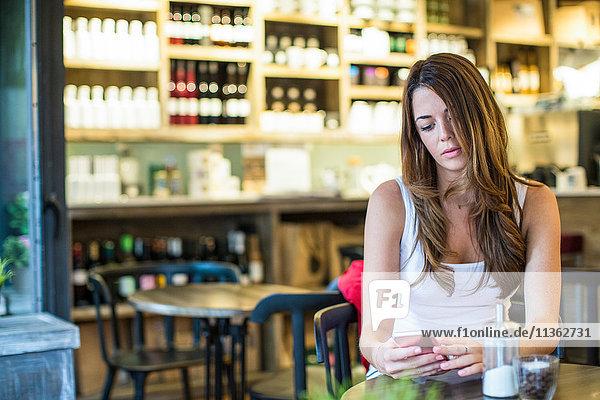 Junge Frau sitzt im Café und liest Smartphone-Texte