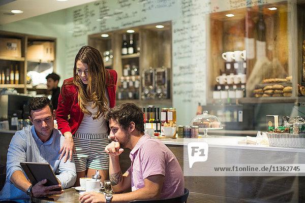 Männliche und weibliche Freunde im Cafe schauen auf das digitale Tablet