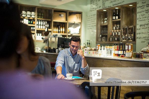 Mann sitzt im Café und redet über Smartphone
