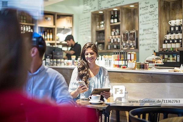 Junge Frau mit digitalem Tablett liest im Café Smartphone-Texte