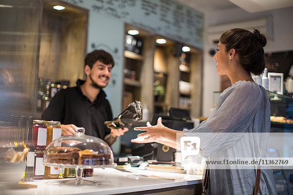 Barista handing baguette to female customer at cafe counter