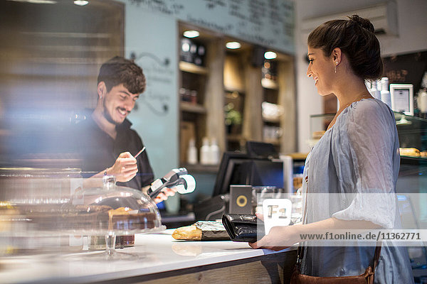 Barista calculating bill for female customer at cafe counter