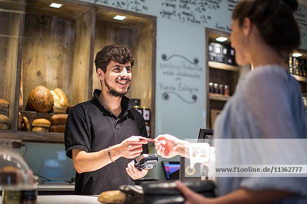 Barista übergibt Kreditkarte an weibliche Kundin am Café-Schalter