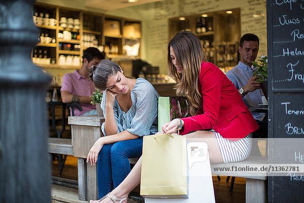 Zwei junge Freundinnen mit Einkaufstaschen unterhalten sich vor dem Café