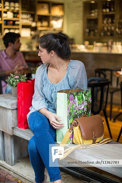 Junge Käuferin sitzt vor einem Café und schaut ihr über die Schulter