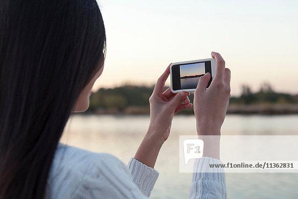 Über-Schulter-Ansicht einer jungen Frau  die in der Abenddämmerung einen Fluss fotografiert  Peking  China