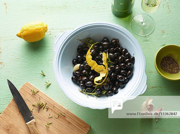 Overhead view of bowl of black olives with lemon peel on table