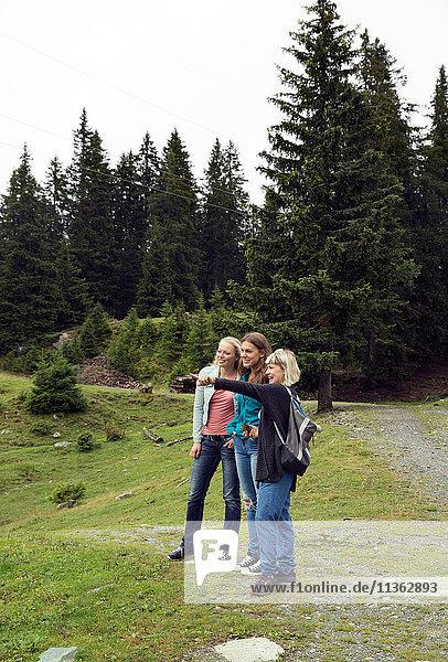 Drei Freundinnen zeigen vom Waldweg aus  Sattelbergalm  Tirol  Österreich