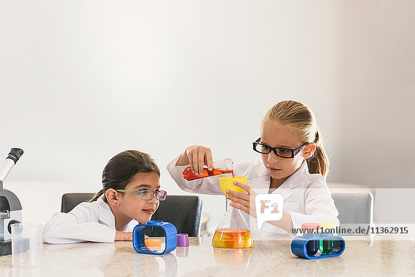 Girls conducting experiments with chemistry set