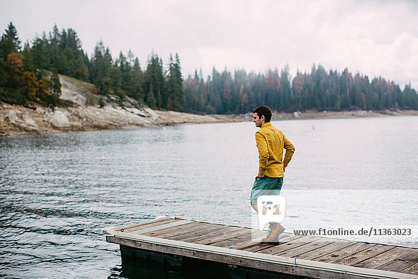 Young man walking on pier at Shaver Lake  California  USA