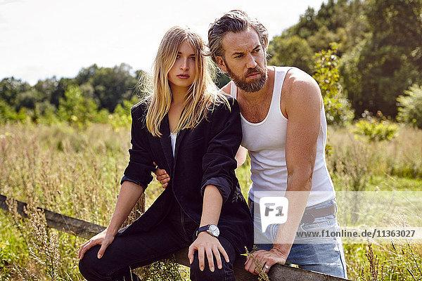 Porträt eines Paares  das auf einem ländlichen Zaun sitzt und zur Seite schaut