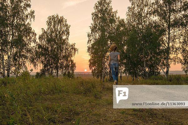 Rückansicht einer Frau  die bei Sonnenuntergang auf einem ländlichen Feldweg läuft