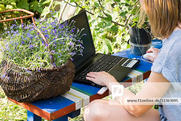 Ausschnitt einer Frau  die im Garten kauert und am Laptop tippt