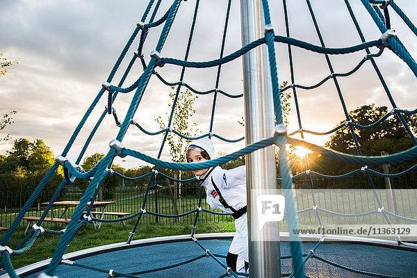 Porträt eines Jungen in Astronautenkostüm  der sich vom Klettergerüst des Spielplatzes aus versteckt und schaut