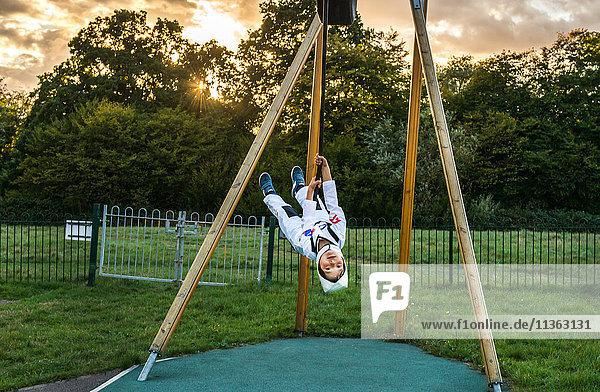 Porträt eines Jungen in Astronautenkostüm  der kopfüber auf einem Spielplatz-Reißverschlussdraht reitet