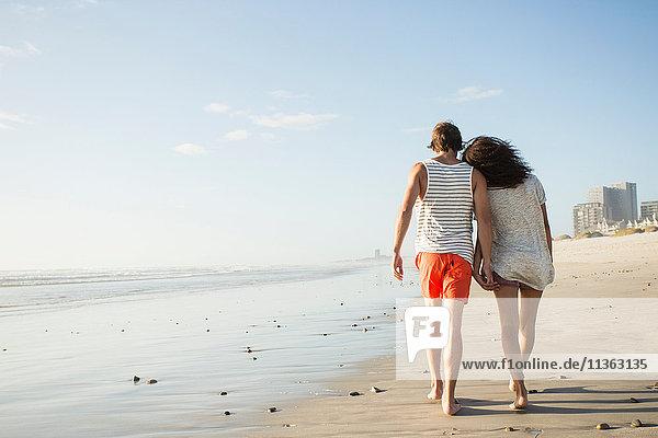Rückansicht eines romantischen jungen Paares beim Strandspaziergang  Kapstadt  Western Cape  Südafrika