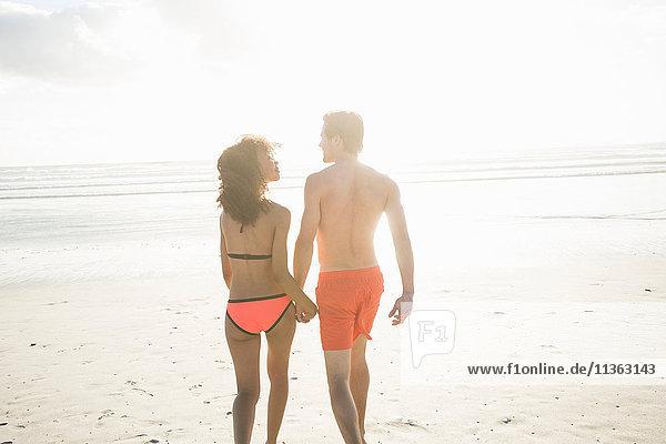 Rückansicht eines jungen Paares in Badebekleidung beim Spaziergang am sonnenbeschienenen Strand  Kapstadt  Western Cape  Südafrika
