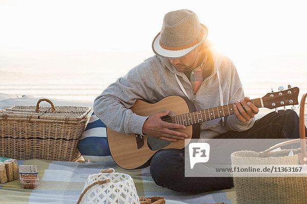 Junger Mann spielt Gitarre am sonnenbeschienenen Strand  Kapstadt  Western Cape  Südafrika