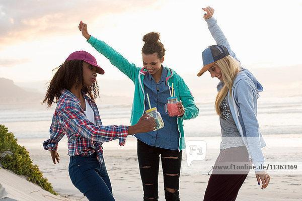 Drei junge Freundinnen tanzen gemeinsam am Strand  Kapstadt  Western Cape  Südafrika