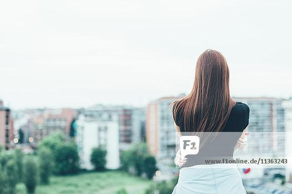 Rückansicht einer jungen Frau mit langen roten Haaren  die über das Stadtbild blickt.