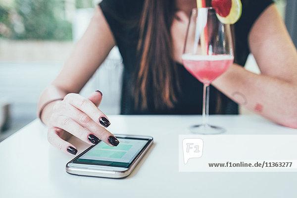 Cropped Schuss der jungen Frau auf dem Bürgersteig Cafe Tisch mit Smartphone Touchscreen