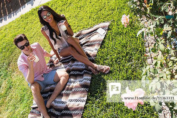 Junges Paar entspannt sich im Freien  sitzt auf einer Decke und hält Getränke