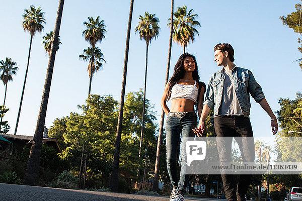 Junges Paar geht im Freien spazieren  hält sich an den Händen  niedriger Blickwinkel