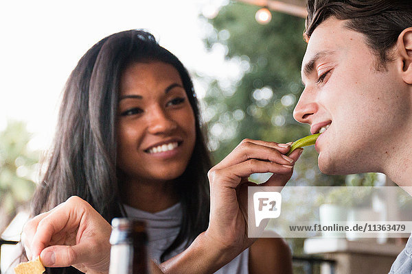 Junges Paar sitzt im Freien  junge Frau füttert jungen Mann  lächelt