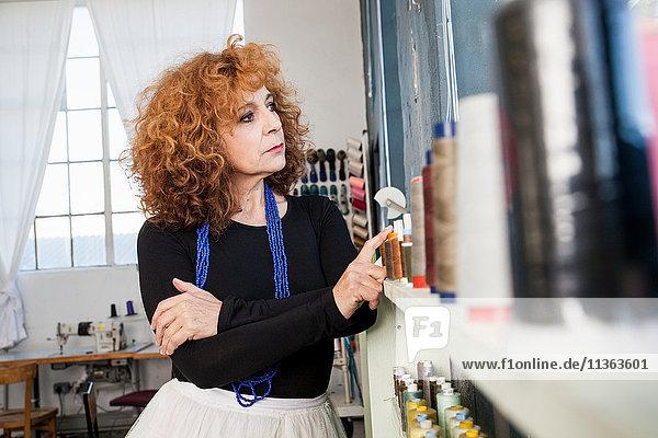 Frau in Nähwerkstatt schaut weg