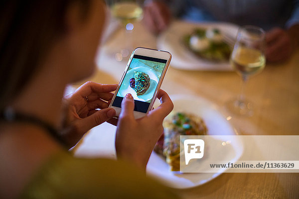 Woman taking photograph of her food on table