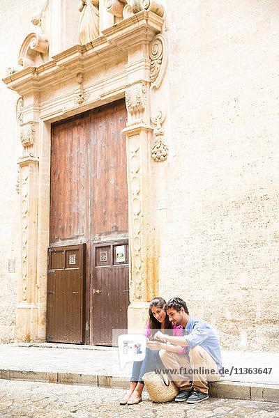 Ehepaar benutzt Mobiltelefon auf dem Bürgersteig  Palma de Mallorca  Spanien
