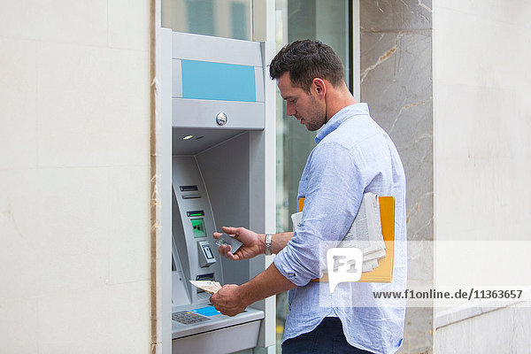 Mann beim Bargeldbezug am Geldautomaten