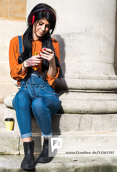 Young woman sitting beside pillar  wearing headphones  holding smartphone