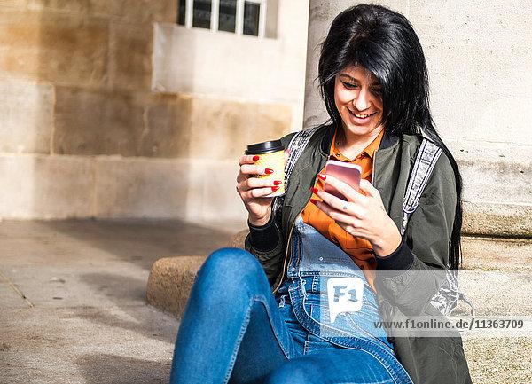 Junge Frau sitzt neben einer Säule  hält eine Kaffeetasse zum Mitnehmen in der Hand und schaut auf ein Smartphone