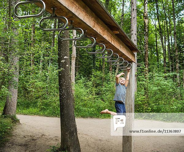 Junge hängt an Affenstangen auf dem Spielplatz