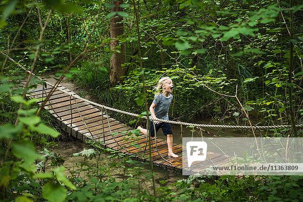 Junge läuft über eine Fussgänger-Seilbrücke im Wald