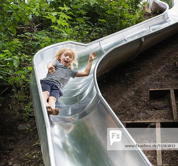 Junge rutscht die Spielplatzrutsche hinunter