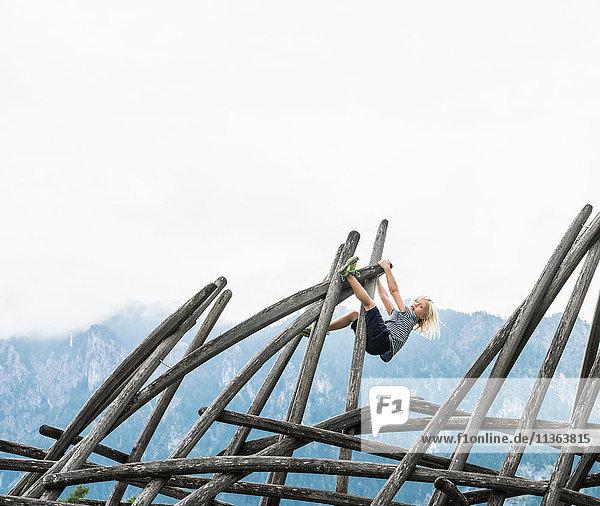 Junge klettert an Holzkonstruktion auf Spielplatz  Füssen  Bayern  Deutschland