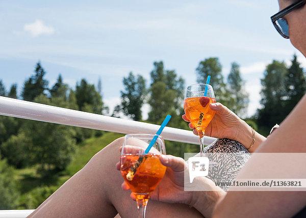 Frauen sitzen mit Cocktails