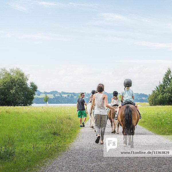 Rückansicht von Eltern  die Kinder zu Pferd führen  Füssen  Bayern  Deutschland