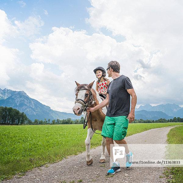 Vater führt Tochter reitendes Pferd  Füssen  Bayern  Deutschland