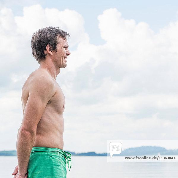 Mann am See schaut lächelnd weg