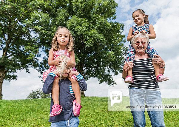 Großmutter und Enkel tragen Mädchen auf den Schultern  Füssen  Bayern  Deutschland
