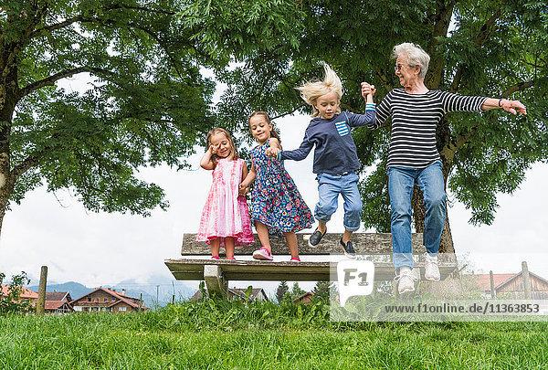 Großmutter und Enkelkinder in der Luft beim Sprung von der Parkbank  Füssen  Bayern  Deutschland